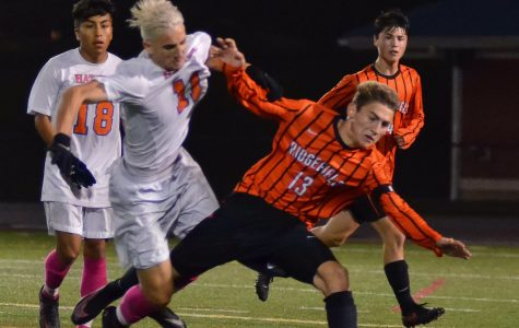 Senior Kevin Spennato and a Ridgefield player fight for the ball during the Hatters' senior night game.
