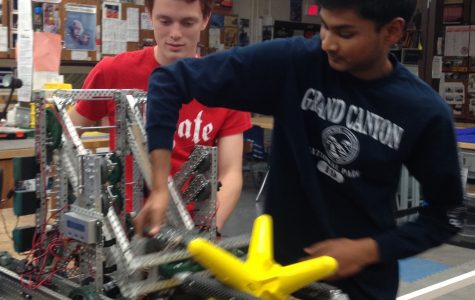 Patrick Cherry (left) and Fawaaz Shaffeeullah (right), senior Mad Hatters' tinker with their robot.