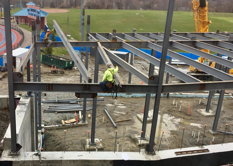 Construction workers erect steel beams, the skeleton for new Freshman Academy.