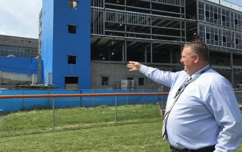 Principal Dan Donovan takes a reporter around on a tour of construction. Here, he is looking at the front of the new Freshman Academy.