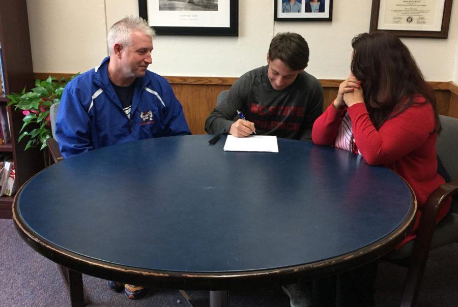 Jakob Camacho signs his National Letter of Intent to North Carolina State University alongside Coach Ricky Shook and Mom Estela Camacho