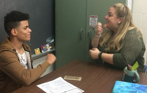 Freshman Raudy Grullon signs with new ASL teacher Jessica Prunty. The course was revived after a year's absence.