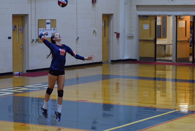 Megan Mercer serves during one of the varsity volleyball games.