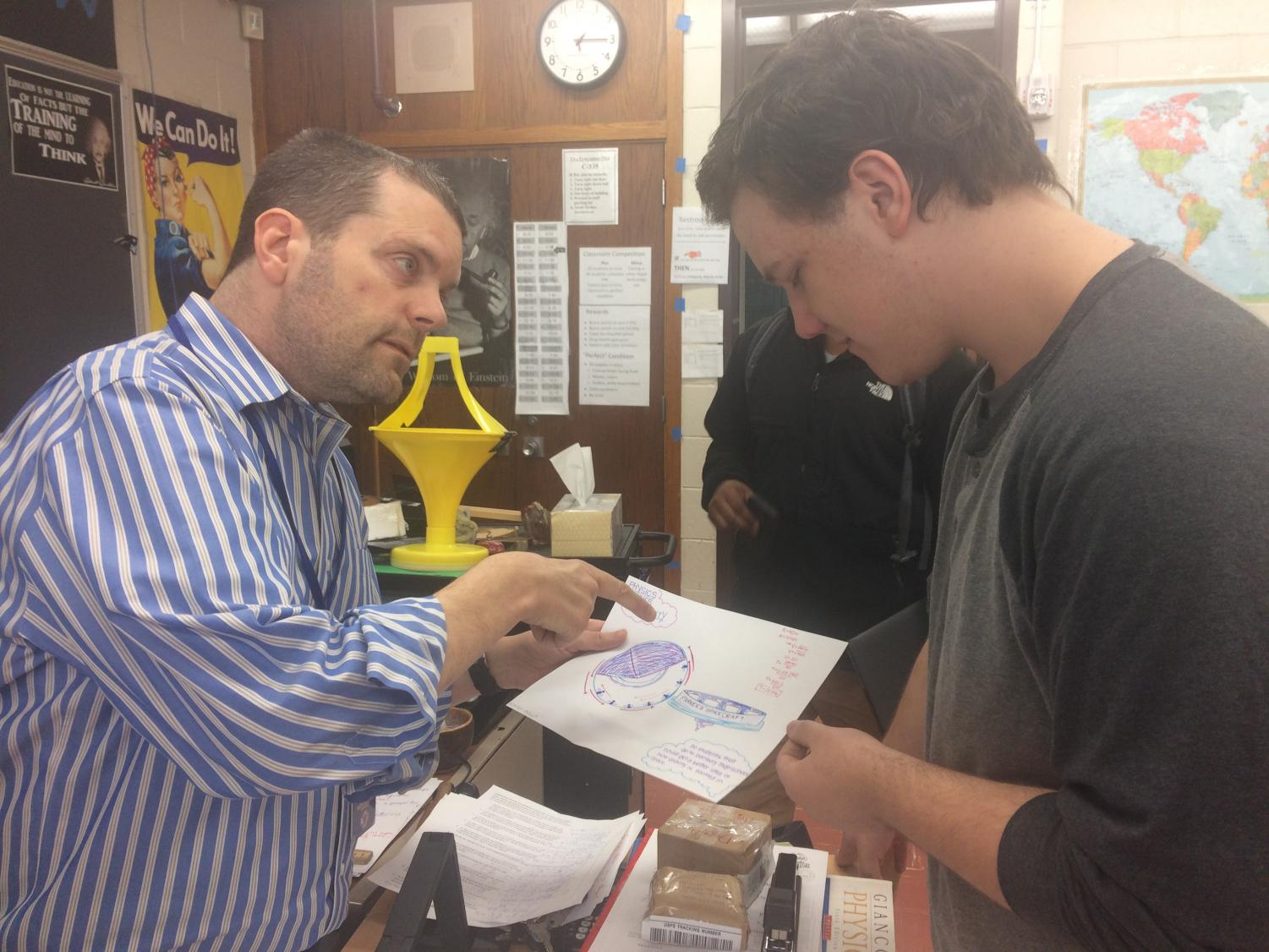 Physics teacher Jameson Parker works on a physics problem with Trevor Roos. Parker is up front with his students about Kennedy's Disease and how it affects him.