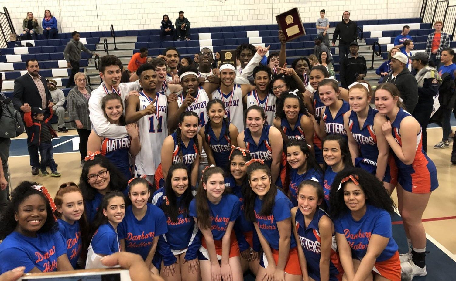 The Danbury boys' basketball team celebrates its FCIAC championship win over Trumbull with fans and cheerleaders.
