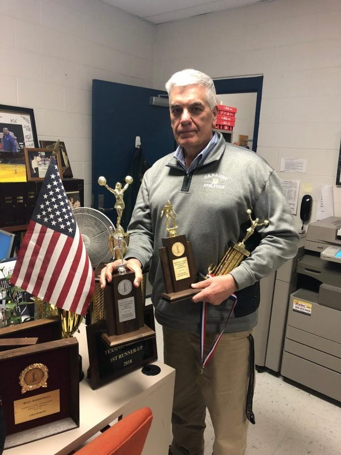 Athletics Director Chip Salvestrini shows some of the trophies won by DHS winter sports teams.