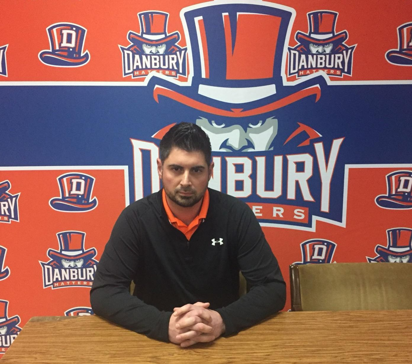 Coach Augustine Tieri sits in front of Danbury's new backdrop to meet with the press after it was announced today that he has been named head football coach.