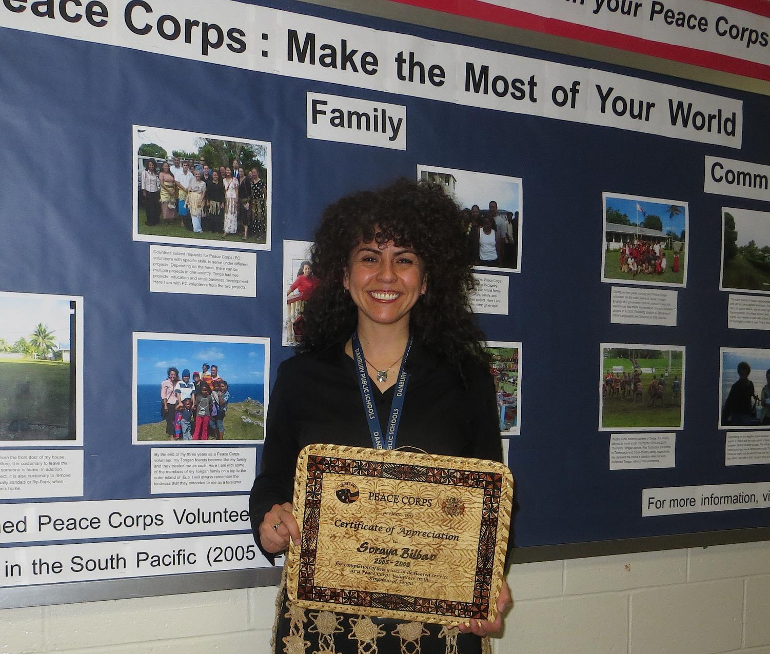 ESL teacher Soraya Bilbao stands before the bulletin board that she produced to commemorate Peace Corps Week. Bilbao presented to several classes about her own Peace Corps experience in the Kingdom of Tonga in the South Pacific.