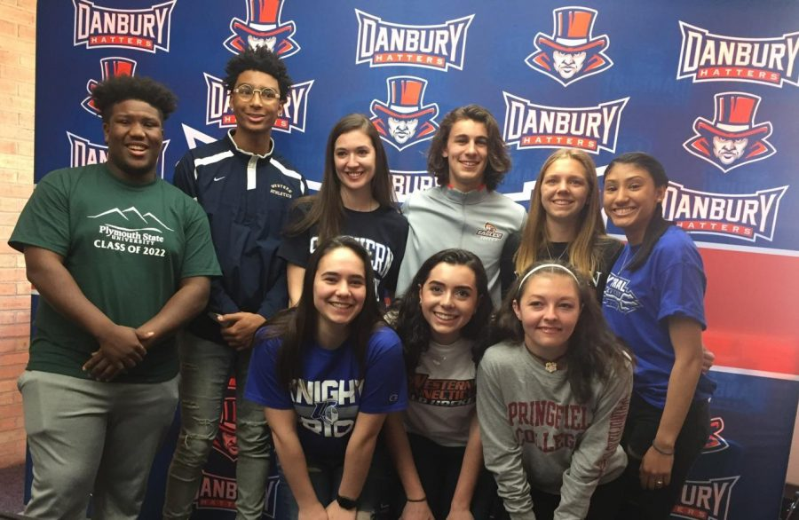 The 9 athlete signees stand together for a picture.