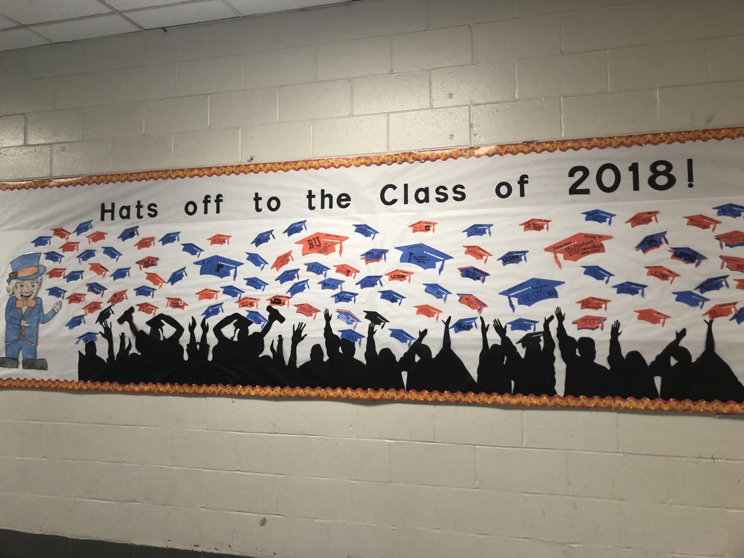 Students post their college decisions on graduation hats located on a bulletin board outside of the cafeteria.