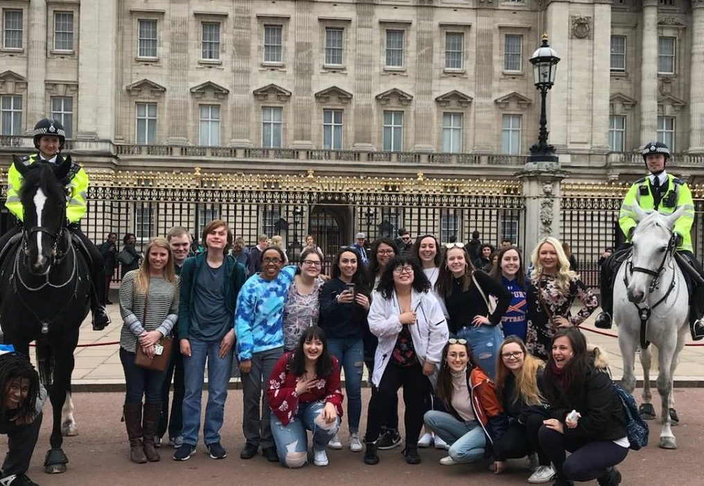 English teachers Arielle Fischer, left, and Danielle Costello, right, stand with their DHS charges in front of Buckingham Palace during the group's Spring Break trip to England.