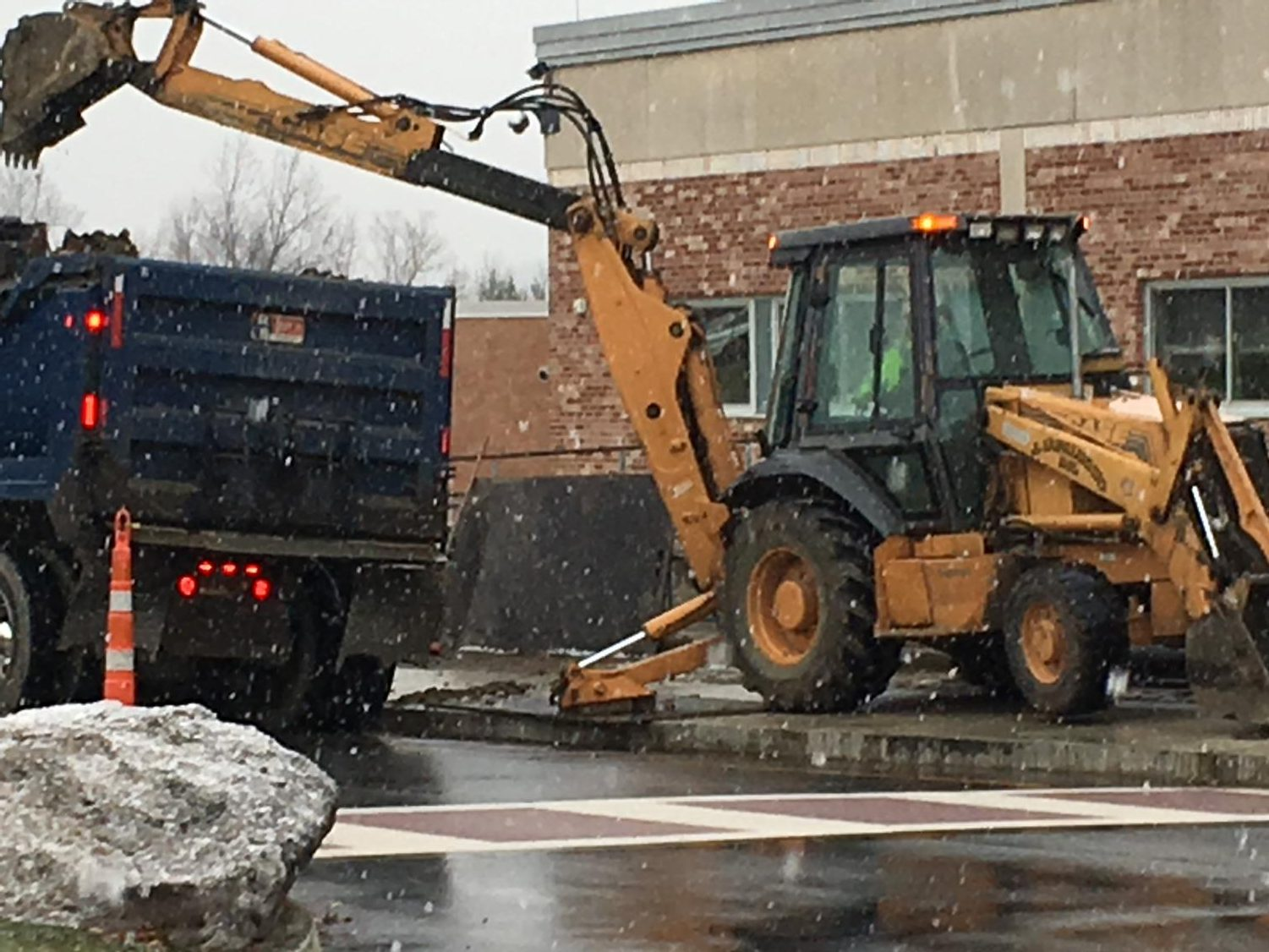 A city building crew works on repairing a water leak that is affecting Eric Savoyski's robotics classroom. The crew has had to excavate to install proper drainage infrastructure.