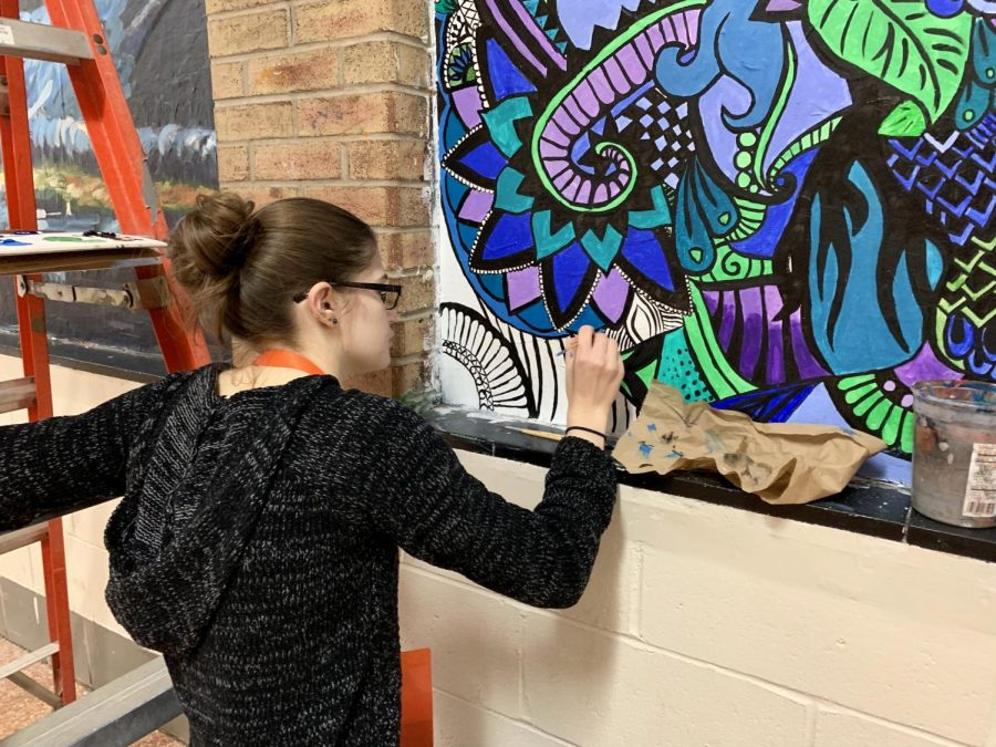 Alumna+Allison+Fiddner+works+on+her+mural+next+to+the+library+Monday%2C+Dec.+10.+She+began+the+mural+last+year+and+returned+this+year+to+put+on+the+finishing+touches.