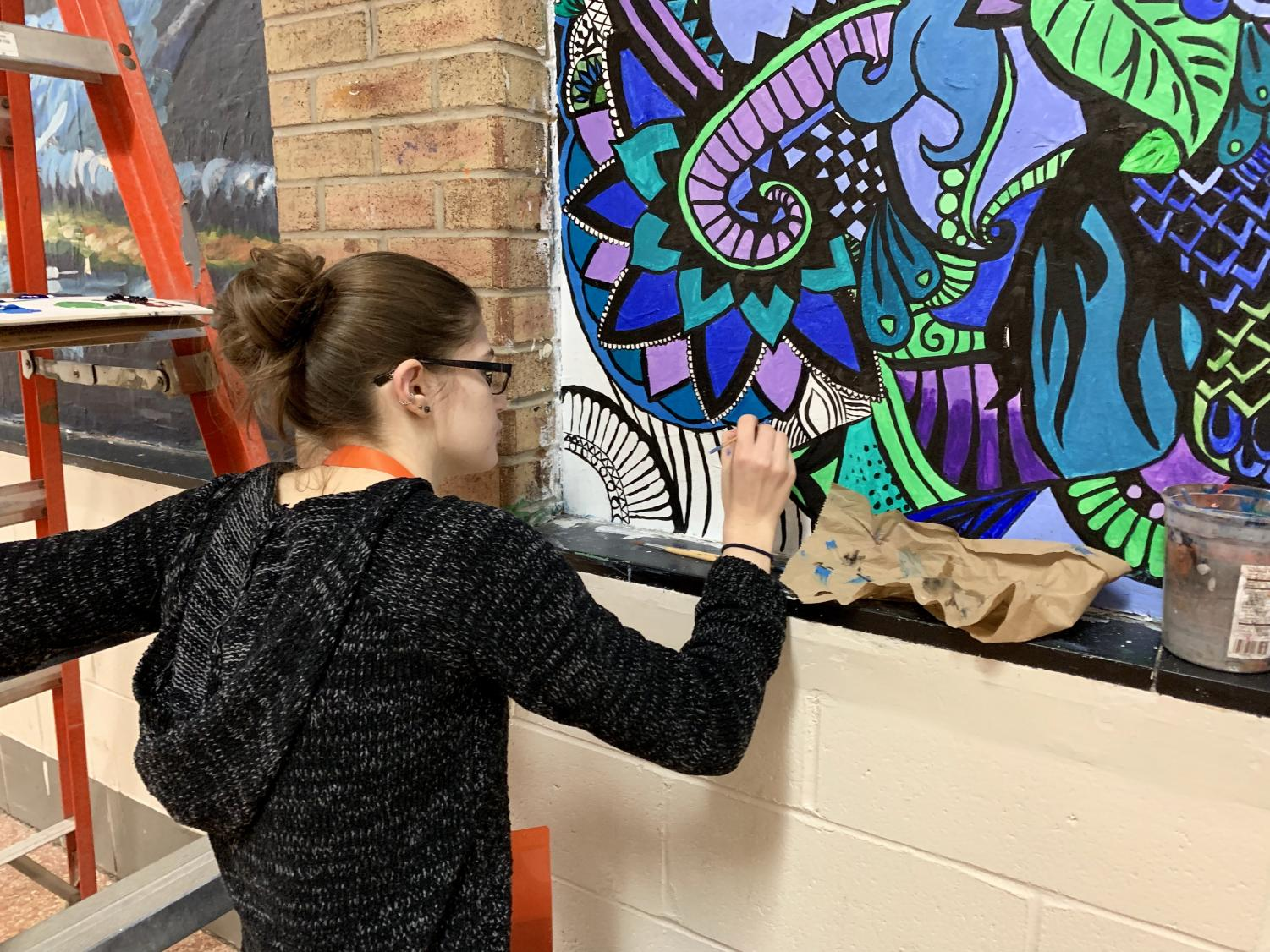 Alumna Allison Fiddner works on her mural next to the library Monday, Dec. 10. She began the mural last year and returned this year to put on the finishing touches.