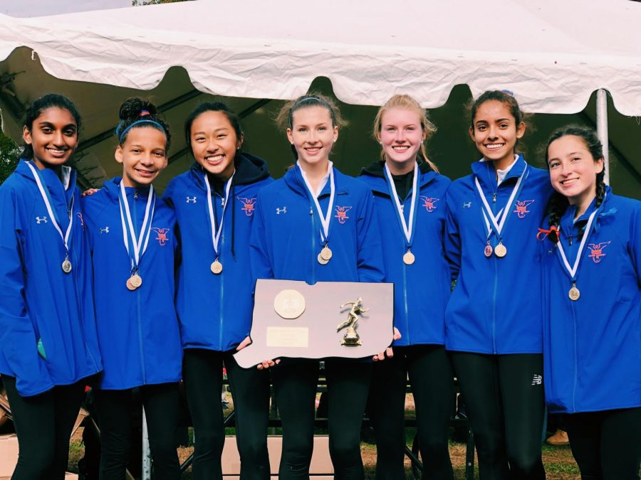 The+girl%27s+cross-country+team+stands+with+its+plaque+from+a+successful+Class+Double+LL+title+win.+Many+of+the+runners+are+now+competing+in+the+indoor+track+season.