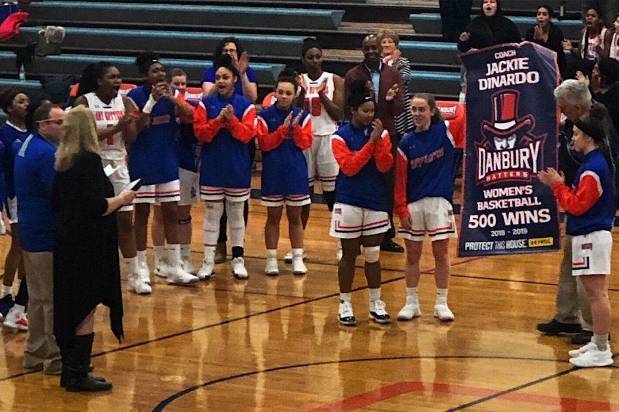 The Lady Hatters and Athletics Director Chip Salvestrini present a banner to Coach Jackie DiNardo commemorating her 500th win as a Connecticut high school girls' basketball coach. She joins elite company in achieving the milestone.