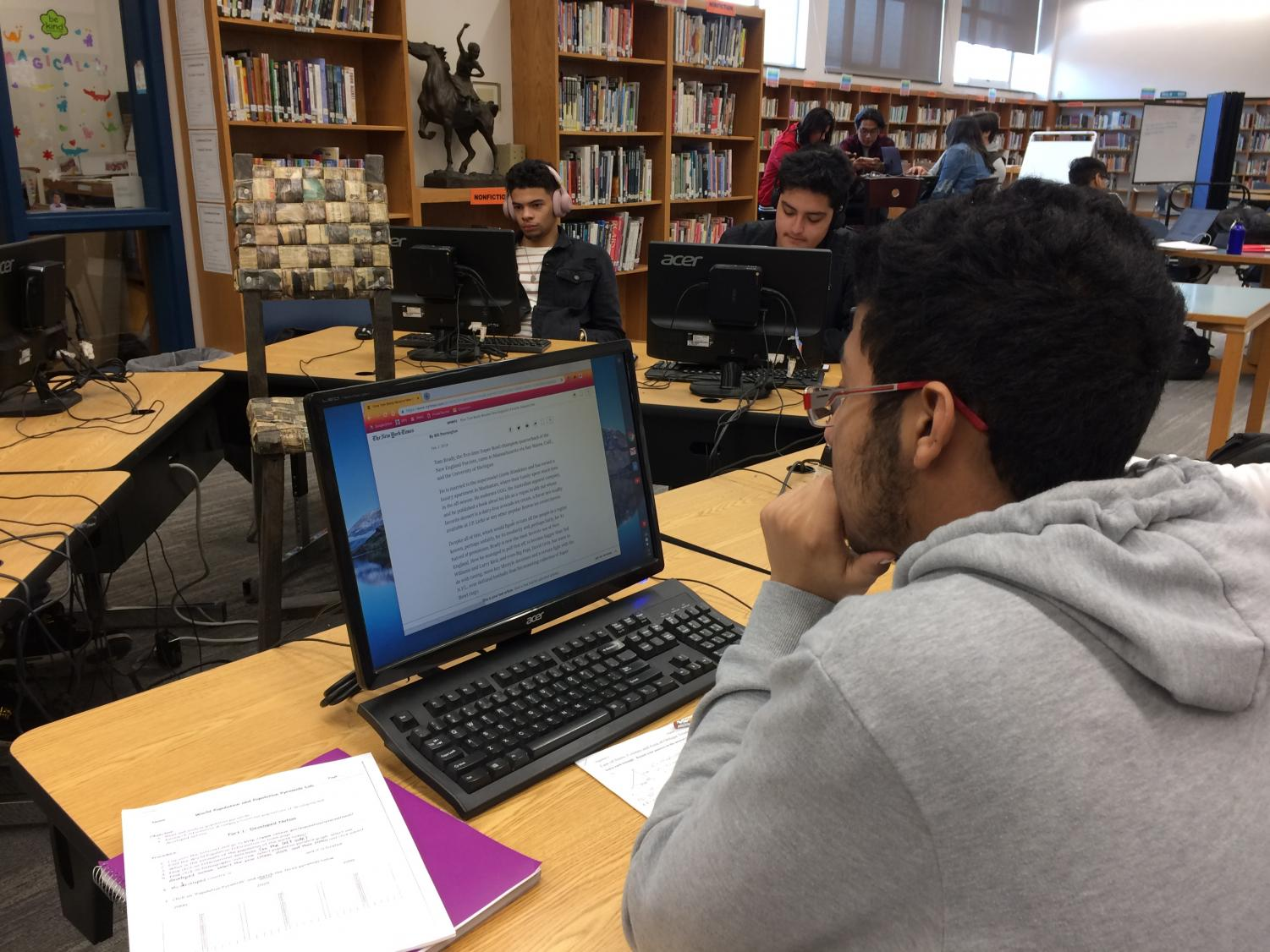 Senior Angel Almonte in the LLC reads a New York Times article about Patriots quarterback Tom Brady becoming New England's favorite adopted son.