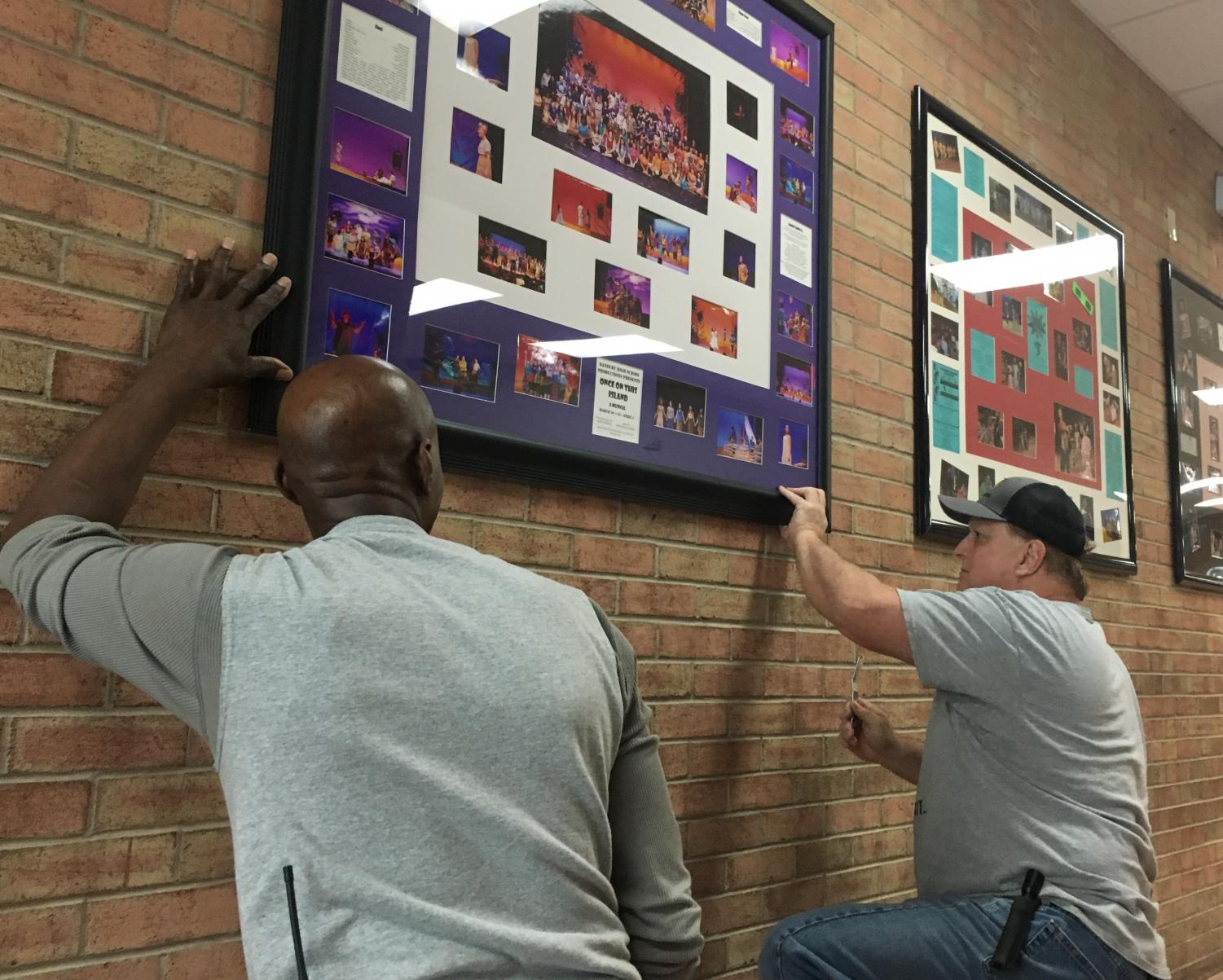 Billie Anderson, left, and Mike Morrison hang DHS  Productions' collages of