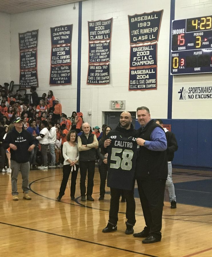 Austin Calitro stands with principal Dan Donovan during a half-time ceremony celebrating the Seattle Seahawk linebacker's return to Danbury and his alma mater for a visit.