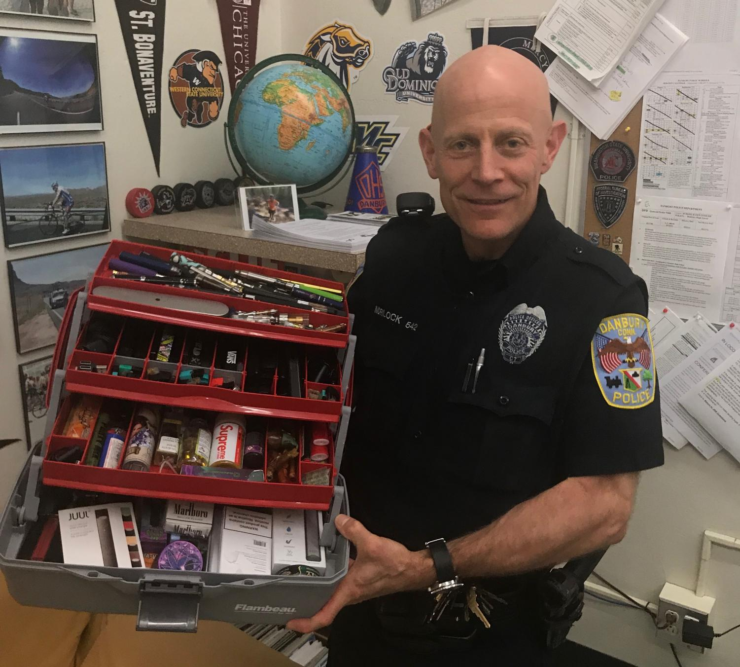 Officer Morlock stands with the collection of vapes, wax pens, pods, juices, carts, and even cigarettes that he's accumulated over his years at DHS. Although when any one of these items is found on a student it is considered evidence to the police, everything seen here he has simply found throughout the school.