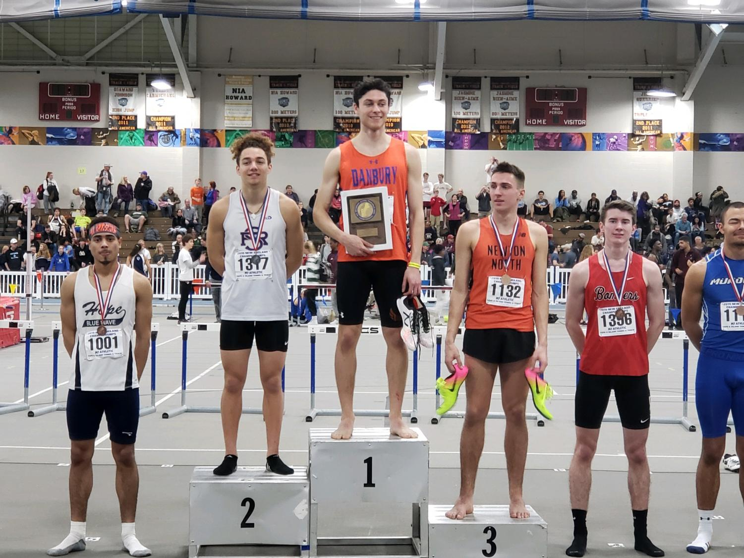 Senior track star Malcolm Going stands with pride after winning first place in the 600m during the indoor New England Championship in Boston on March 2.