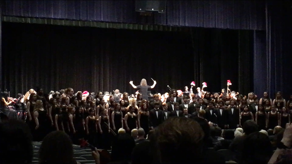 Mary Peters conducts the DHS Symphony Orchestra while Kimberly Russell conducts the DHS Choir in a joint song at the 2019 DHS Winter Concert. The concert also featured the DHS Band.